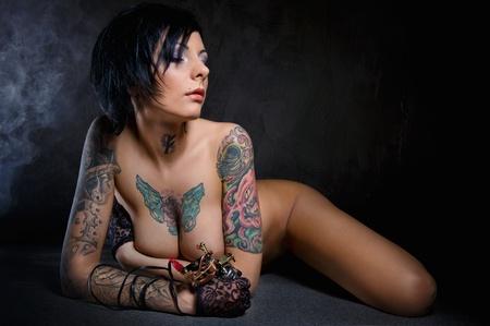 Gyönyörű nő, sok tetoválással pózol beltéri Stock fotó