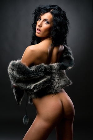 Gorgeous brunette wearing fur coat  posing indoors photo