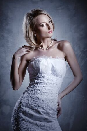 Beautiful blond bride posing indoors photo