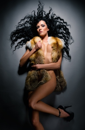 Gorgeous sexy brunette wearing fur vest lying indoors photo