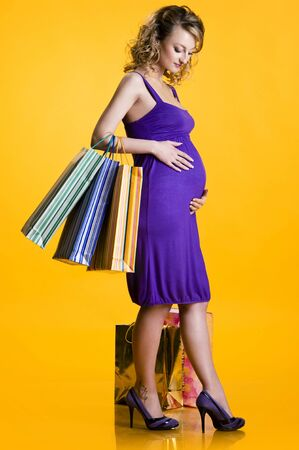 Lovely pregnant woman holding shopping bags over yellow background photo