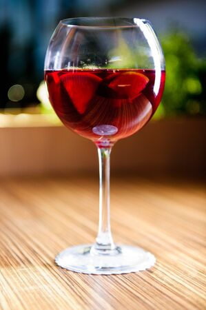 Glass of red wine with fruits photo