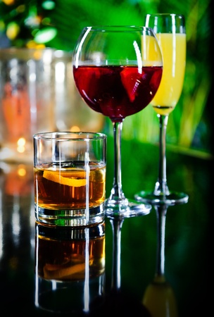 Three different beverages, glass of whiskey, glass of red wine and yellow cocktail  photo