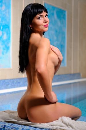 mujer desnuda sentada: Hermosa mujer morena relajarse en la piscina