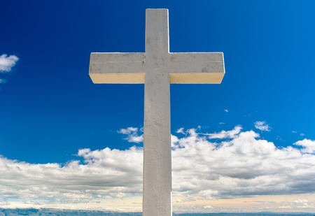tortured: White cross against blue sky and fluffy clouds  Stock Photo