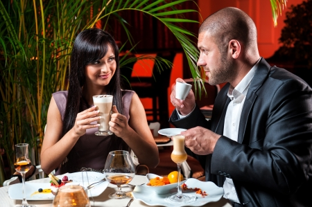 lifestyle dining: Beautiful couple in love drinking coffee at restaurant