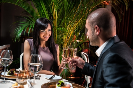 Beautiful couple with glasses of champagne at restaurant on romantic date photo