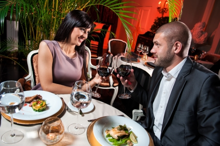 Beautiful couple with glasses of red wine at restaurant on romantic date photo