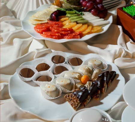 Assortment of fresh fruits and chocolate candies on a table  photo