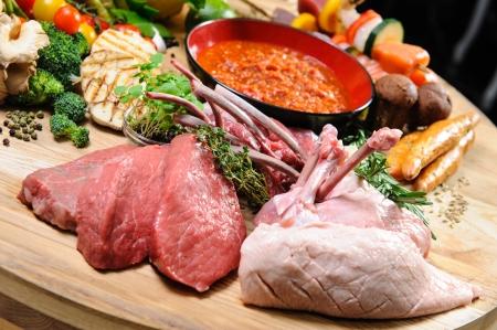 carne de pollo: La abundancia de alimentos crudos en una tabla de madera Foto de archivo