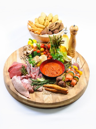 Abundance of raw food on a wooden board and basket of bread over white background photo