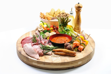 veggie tray: Abundance of raw food on a wooden board and basket of bread over white background