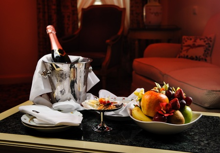 luxury hotel room: Romantic evening with bottle of champagne, sweets and fruits in the hotel room
