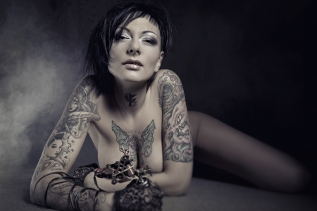 naked woman breasts:  Beautiful woman with many tattoos posing indoors Stock Photo