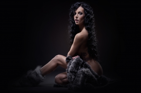 naked woman sitting: Gorgeous sexy brunette with fur coat indoors Stock Photo
