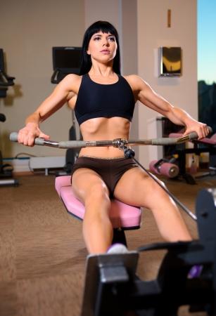 levantando pesas: Mujer joven atractiva que hace ejercicios en el gimnasio
