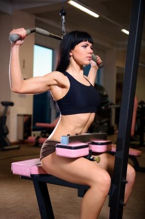 Vonzó fiatal nő csinál gyakorlatok az edzőteremben