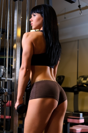 training device: Beautiful young woman working out in fitness club
