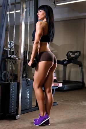 levantamiento de pesas: Hermosa mujer joven que trabaja en el gimnasio