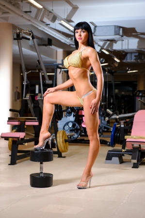 Athletic beautiful woman posing in the fitness club photo