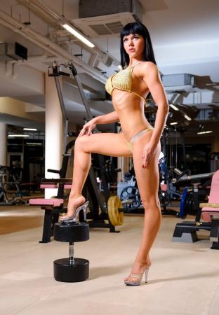 Atlétikai gyönyörű nő pózol a fitness club