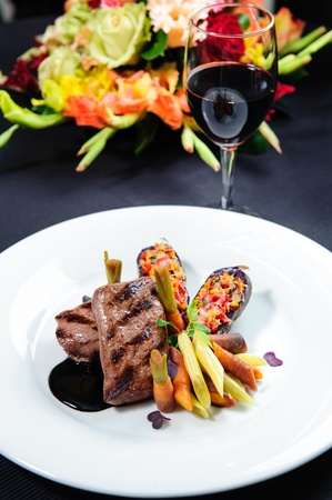 Juicy roe steak on a plate and glass of red wine  photo