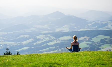 mujer meditando: Joven mujer meditando al aire libre