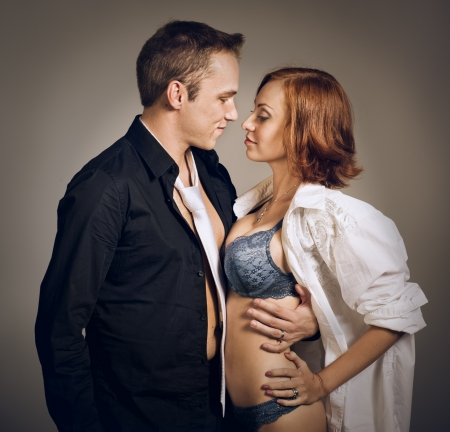 Beautiful young smiling couple in love embracing indoor, studio shot photo