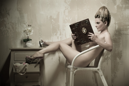 naked legs: Naked woman sitting in a chair reading a book indoors