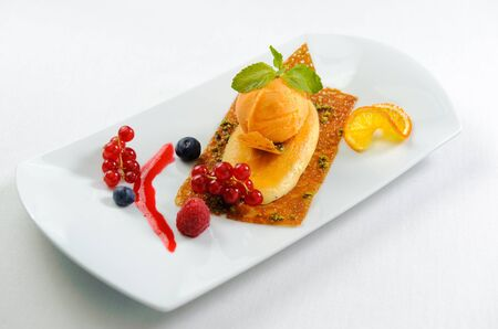 gozinaki: Luscious dessert on a plate. Ice cream ball, biscuit, pistachio in sugar syrup and fresh berries Stock Photo