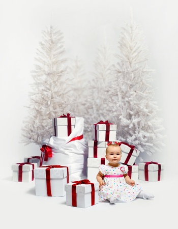 Adorable baby girl over christmas trees and heap of gift boxes background Stock Photo - 16009274