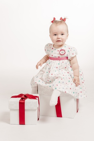 Lovely crying baby girl with two gift boxes over white background photo