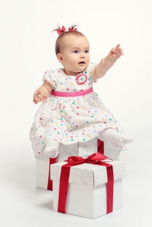 Adorable baby girl with two gift boxes posing over white background photo