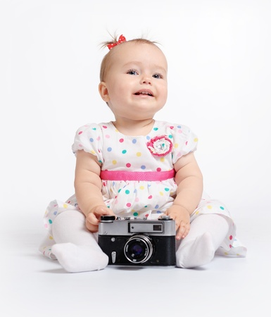 Adorable baby with retro camera over white background photo