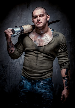 muscular build: Muscular tattooed man with jackhammer posing over grey background