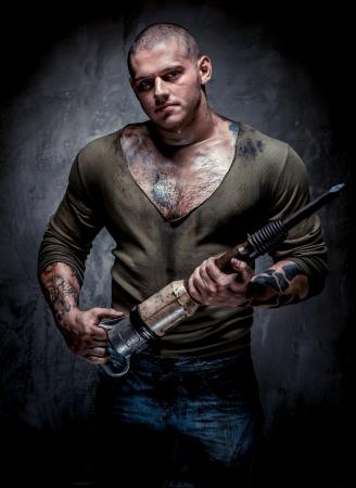 presslufthammer: Muskul�s t�towierten Mann mit Presslufthammer posiert auf grauem Hintergrund Lizenzfreie Bilder