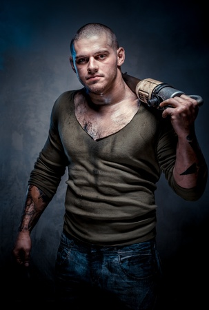 Muscular tattooed man with jackhammer posing over grey background photo