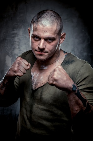 Portrait of young fighter with dirty face and chest photo