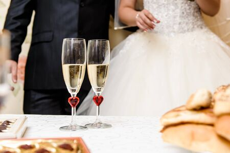 Glasses of champagne and bride and groom on background, selective focus photo
