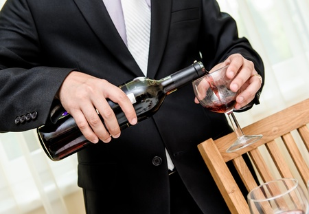 Man pouring red wine from bottle into a glass Stock Photo - 16398865