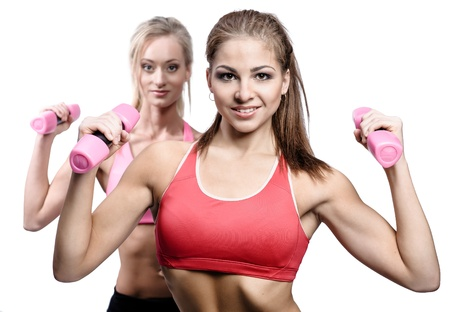 bicep: Two attractive athletic girl with dumbbells