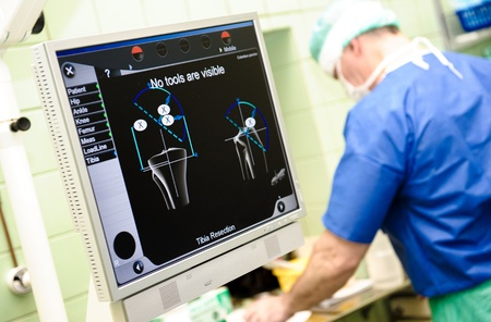 Medical orthopaedic equipment navigation system and surgeon on background at hospital