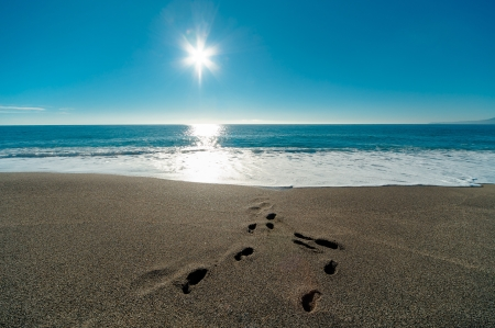 footprint sand: Sunny day, blue sea and footprints in the sand