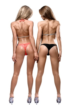 Two athletic girl wearing bikini posing over white background photo
