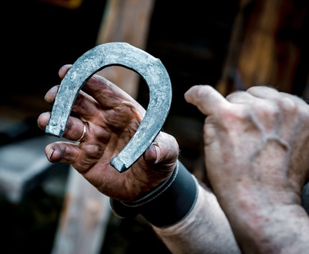 Blacksmith's dirty hands holding horseshoe   photo