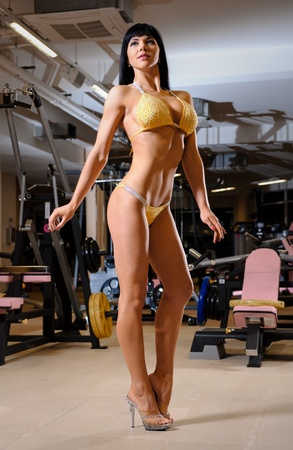 Beautiful athletic young woman posing in the fitness club photo