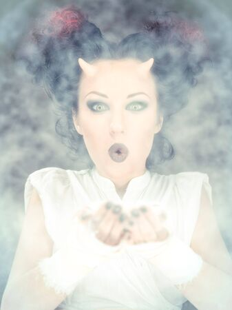 Portrait of devil woman blowing a white powder, conceptual photo photo