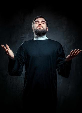 sotana: Retrato del sacerdote contra el fondo oscuro
