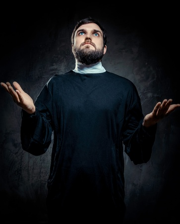 vicar: Portrait of priest against dark background