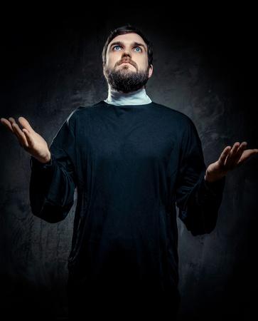 toog: Portret van priester tegen een donkere achtergrond